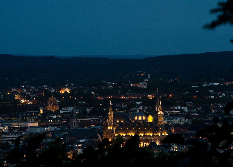 """Der Lousberg ist mit 264 Metern Höhe eine markante Erhebung im Norden der Stadt Aachen. Die Herkunft des Namens ist nicht völlig geklärt. Er könnte von """"lusen"""" (lugen, schauen) stammen, da der Berg einen hervorragenden Rundumblick bietet, oder auf Ludwig den Frommen (Louis), den Sohn Karls des Großen, zurückgehen. Ein weiterer Erklärungsansatz bezieht sich auf den Ausdruck """"lous"""" im Aachener Dialekt für schlau"""